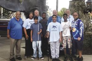 Robert Chaplin, Everglades photographer (4th from left); Jim Sutton, Exec. Director of the Everglades Association (4th from right); and J.R. Young, General Mgr, Bass Pro Miami (2nd from right) with volunteers and some very lucky youngsters with their new fishing gear donated by Bass Pro Shops.