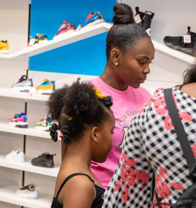 Laury Henryn, a volunteer from FIU's Alpha Kappa Alpha Sorority helps Tyla Bailey and her family pick out the right pair of shoes at the You Are Not Forgotten Shoe Drive.