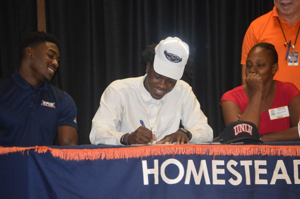 Rahmod Smith (in white) smiles as he commits to FAU.  He was joined by his brother and his mother.