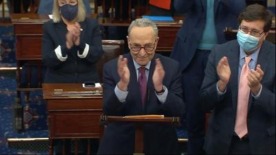 Senate Majority Leader Chuck Schumer of N.Y., leads a round of  applause for support staff as he speaks before the final vote on the Senate version of the COVID-19 relief bill in the Senate at the U.S. Capitol in Washington, Saturday, March 6, 2021.