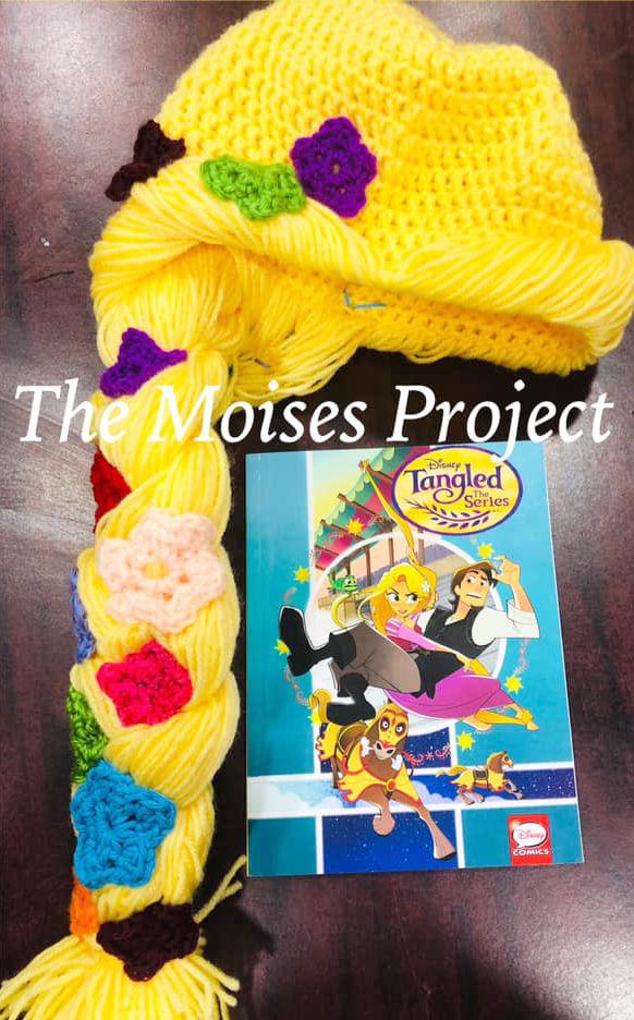 """Rapunzel"" hat alongside a copy of the Disney book of ""Tangled""."