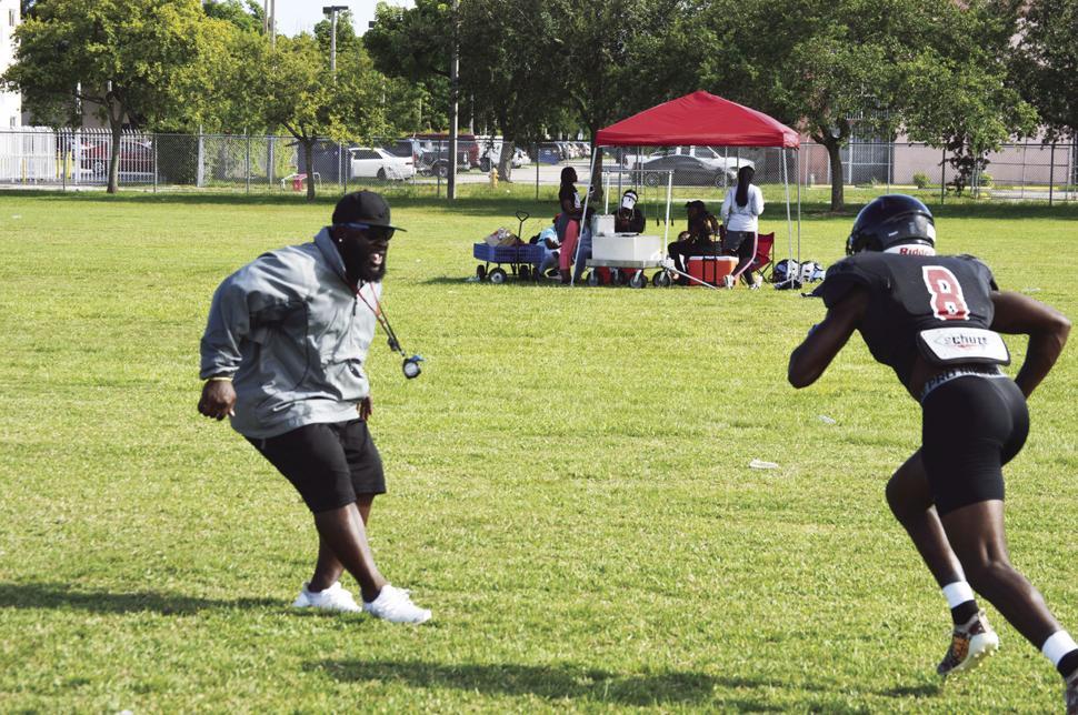 Spartans Head Coach Sedrick Irvin running drills with Tyrique Stevenson.