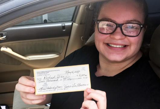 Racheal Diaz, SDHS senior, smiling displays her scholarship check.