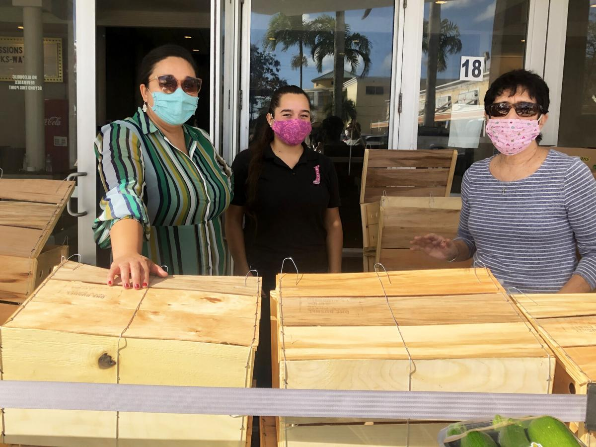 Katherine Rubio and Karina Escalante of the Seminole Theatre were pitching in with Dr. Linda Fagan to prepare 150 baskets for  distribution to local families.