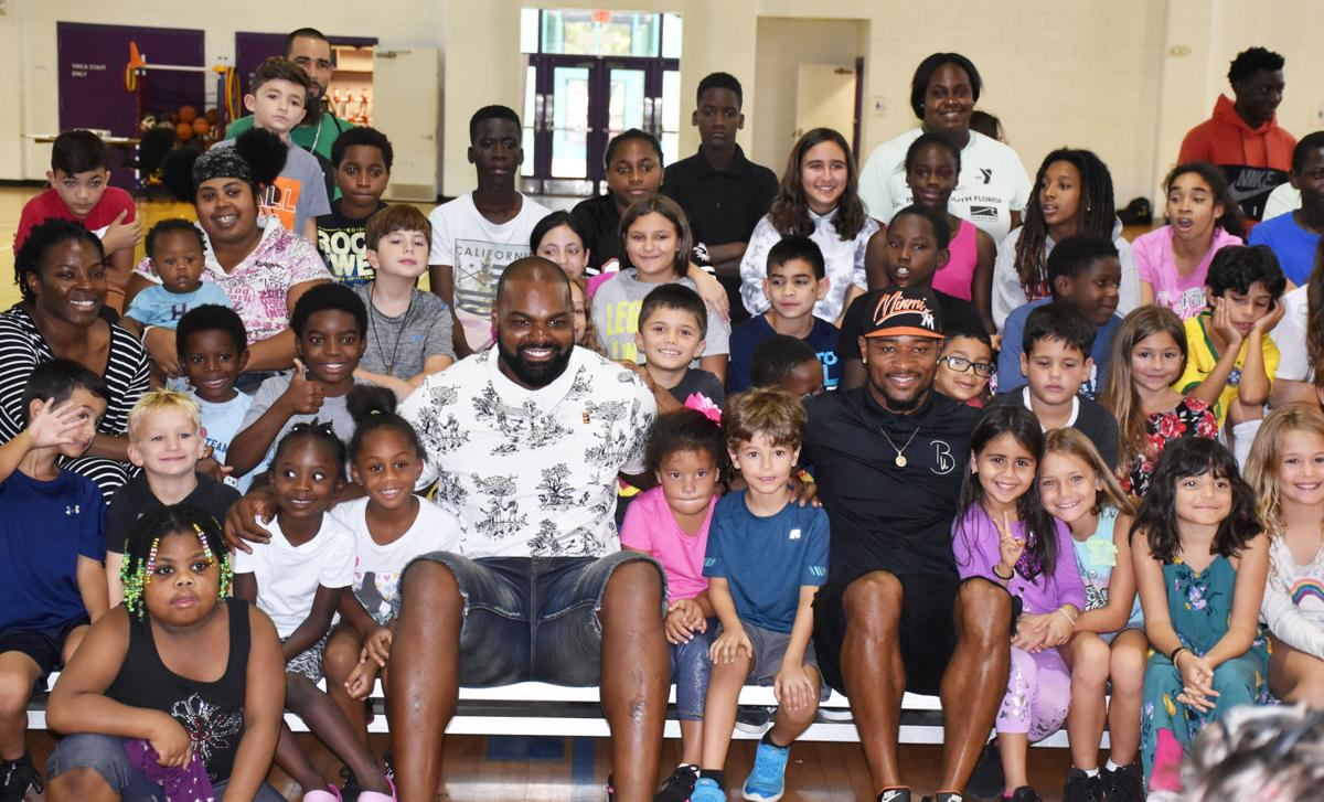 Former NFL football players Michael Oher (white shirt) and  Jamarca Sanford (black shirt) came to Homestead to motivate local students for a successful school year.  Above:  Oher and Sanford pose with students and YMCA staff.  Below: Oher and Sanford give a  backpack and encouragement to a student.