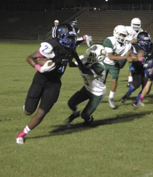 <p>Dauphin's Mykel Johnson stiff-arms a Coppinville defender on his way to a 31-yard touchdown run during the eighth grade game.</p>