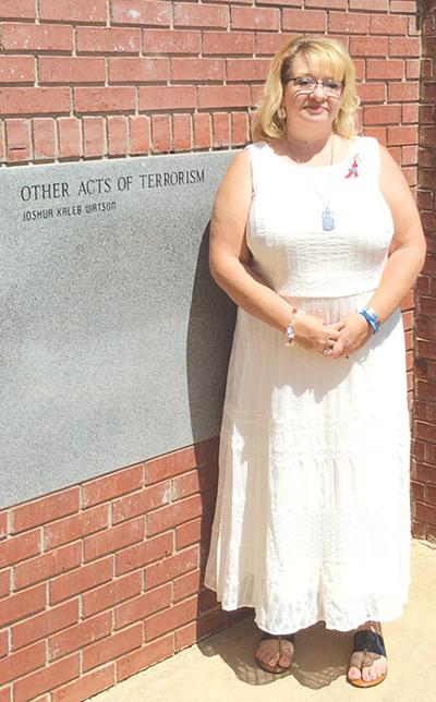 Sheila Watson, stands next to her son's name after an unveiling ceremony