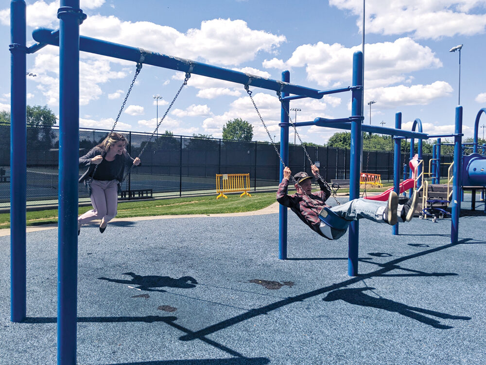 Waves, Inc. Community Relations and Development Director Staci Davis, left, swings with Waves resident John Lynch