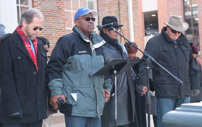 Historian Eric Jacobson, Pastor Hewitt Sawyers, Pastor Chris  Williamson and Pastor Kevin Riggs clasp hands as Pastor  Sawyer delivers a prayer at the MLK Jr. Celebration in  downtown Franklin