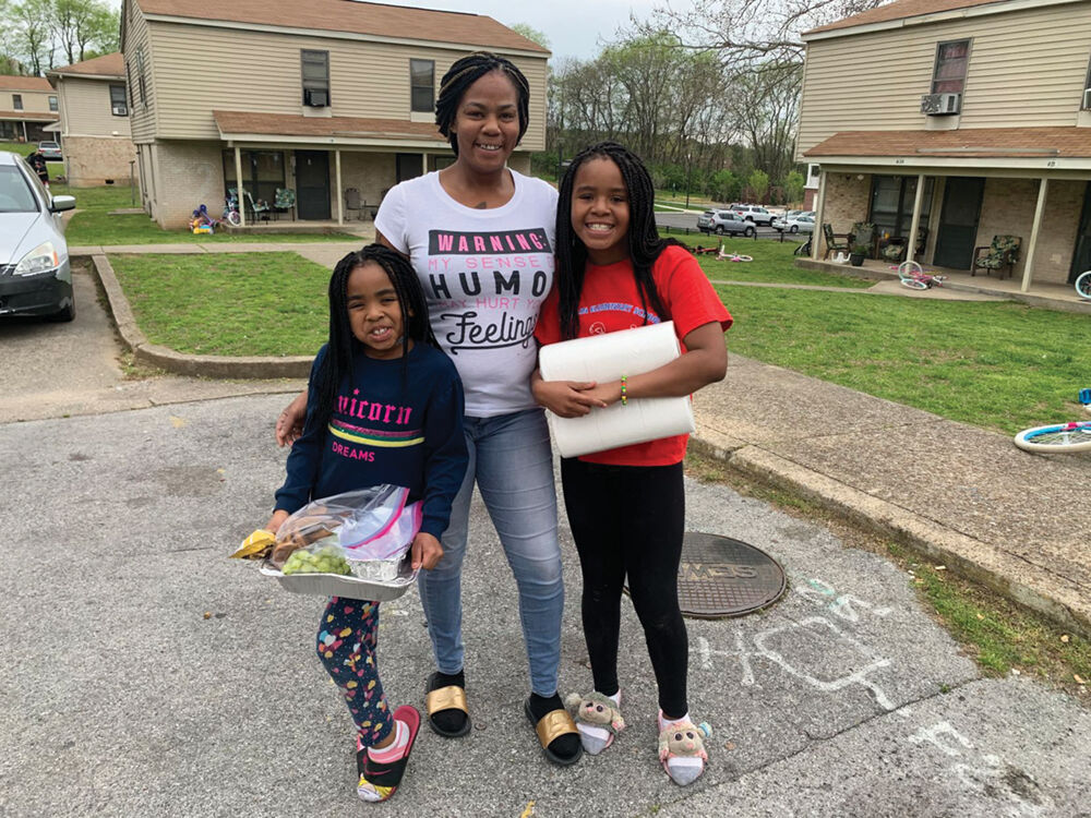 Cynthia Davis and her two daughters, Delilah and De'Andrea, receive a meal and household necessities from FrankTown Open Hearts.