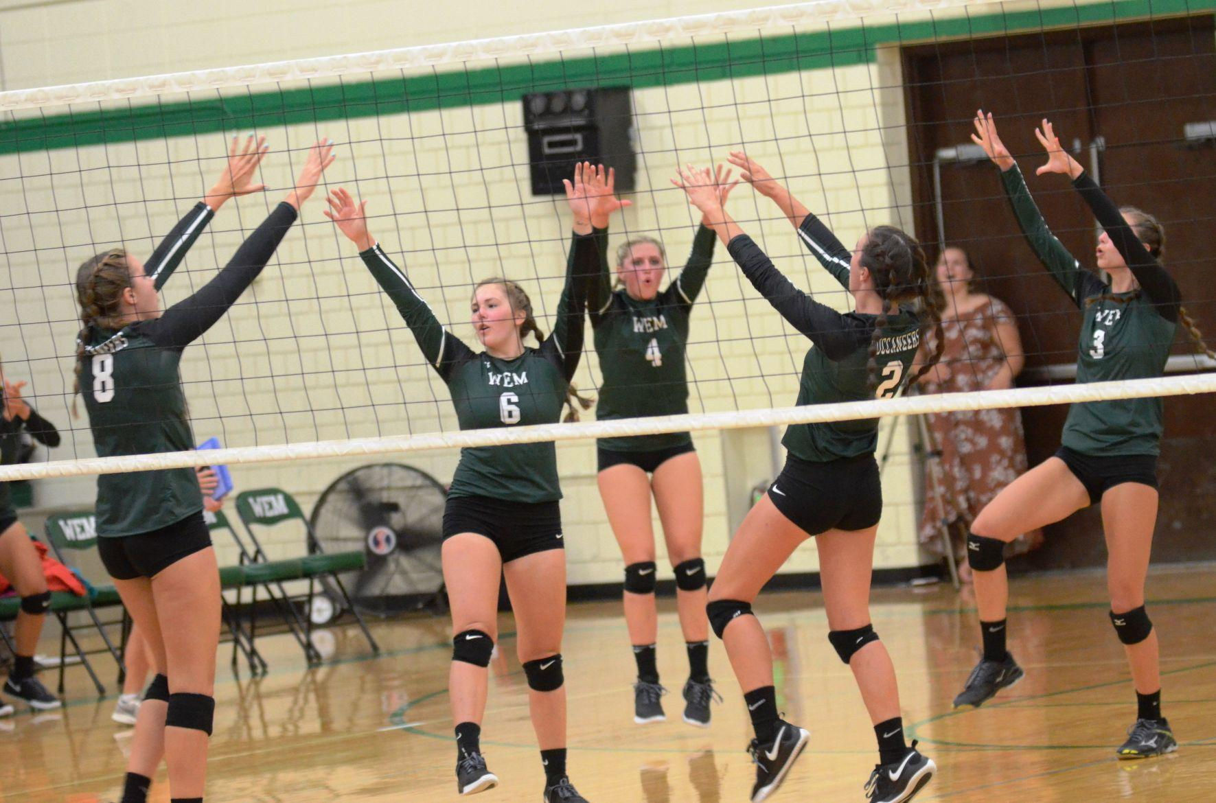WEM volleyball celebrates a block