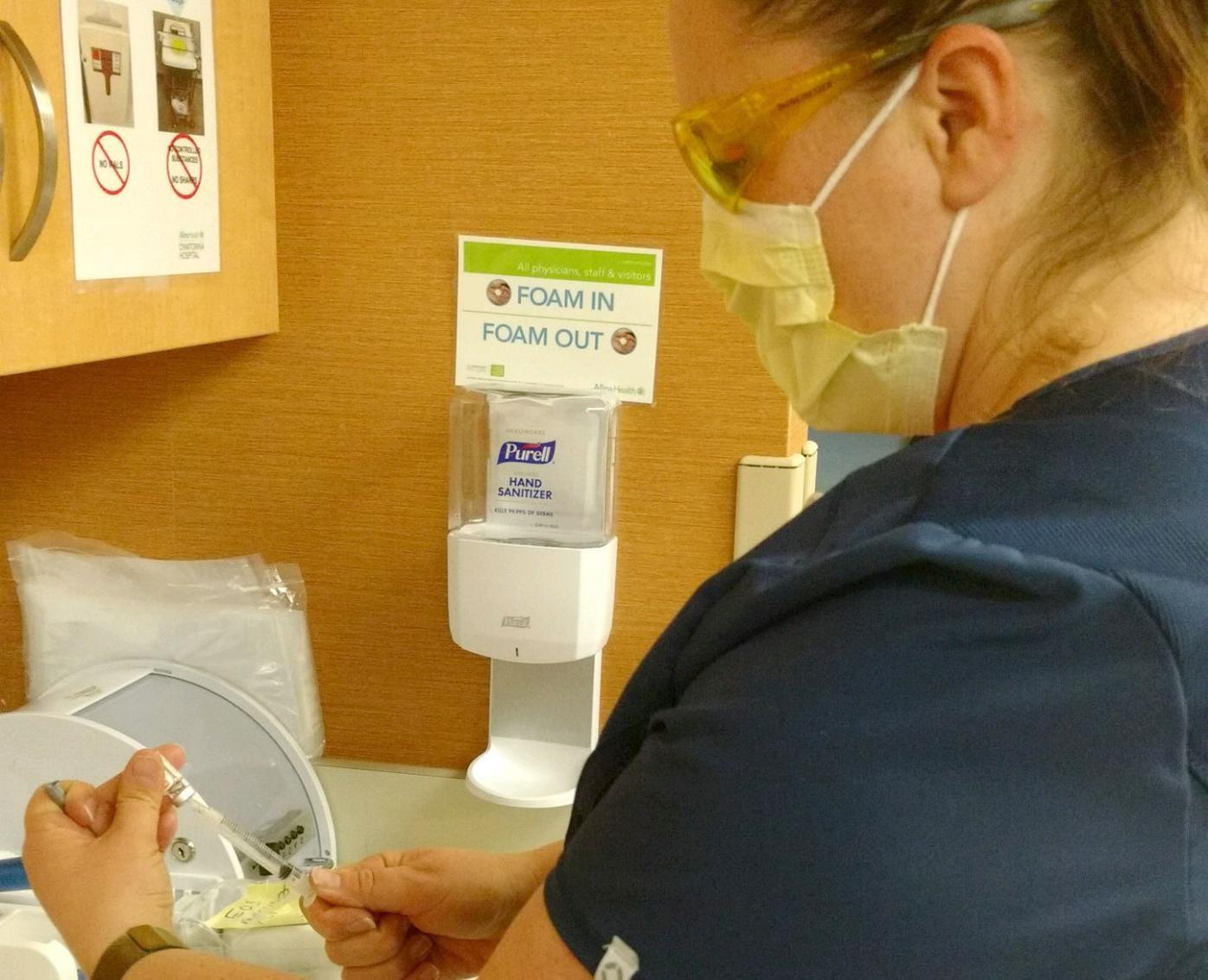 Trisha draws medicine out of vial
