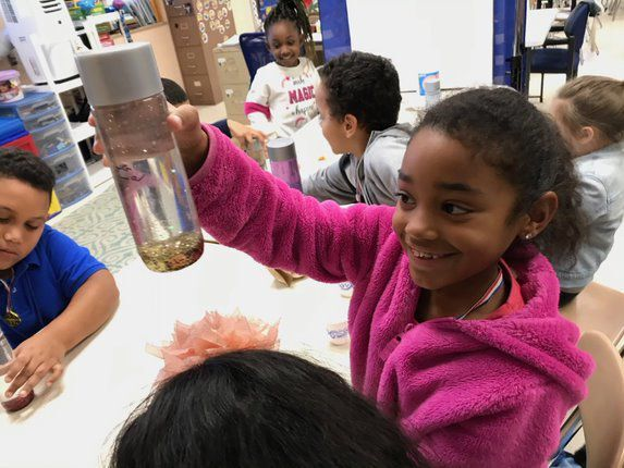 Arthur Street student holds settling jar
