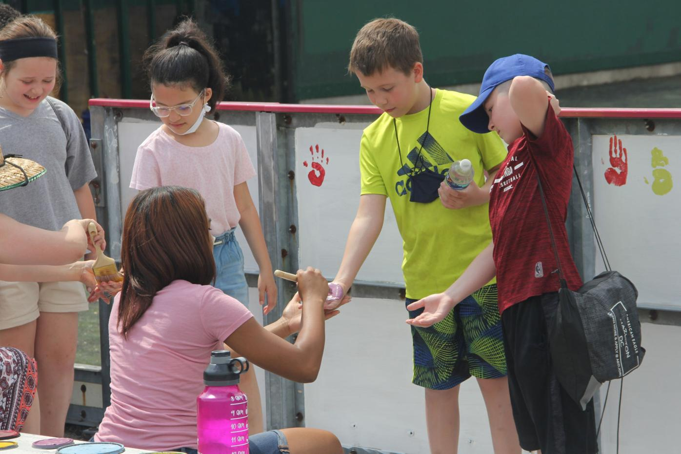 ICS_Junior,_Ashley_Taveras,_paints_4th_graders'_hands_for_handprints_on_the_wall