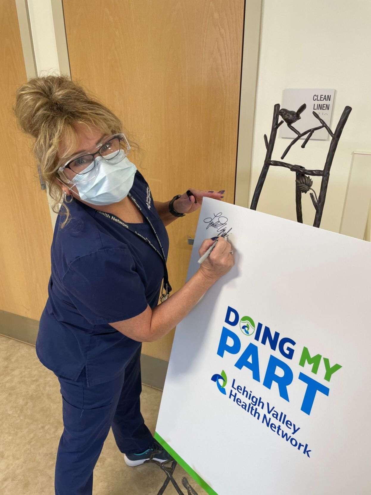 Hazleton hospital employee signs poster after being vaccinated for COVID-19