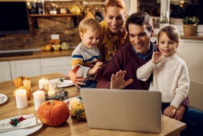 Happy family having video call before Thanksgiving meal at home.