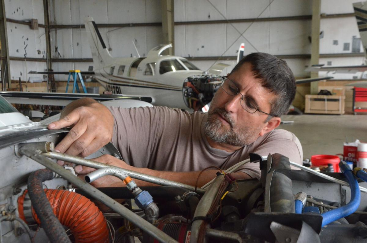 Jamey Gullatt works on a aircraft inside of a hangar at Statesville Regional Airport on Friday.