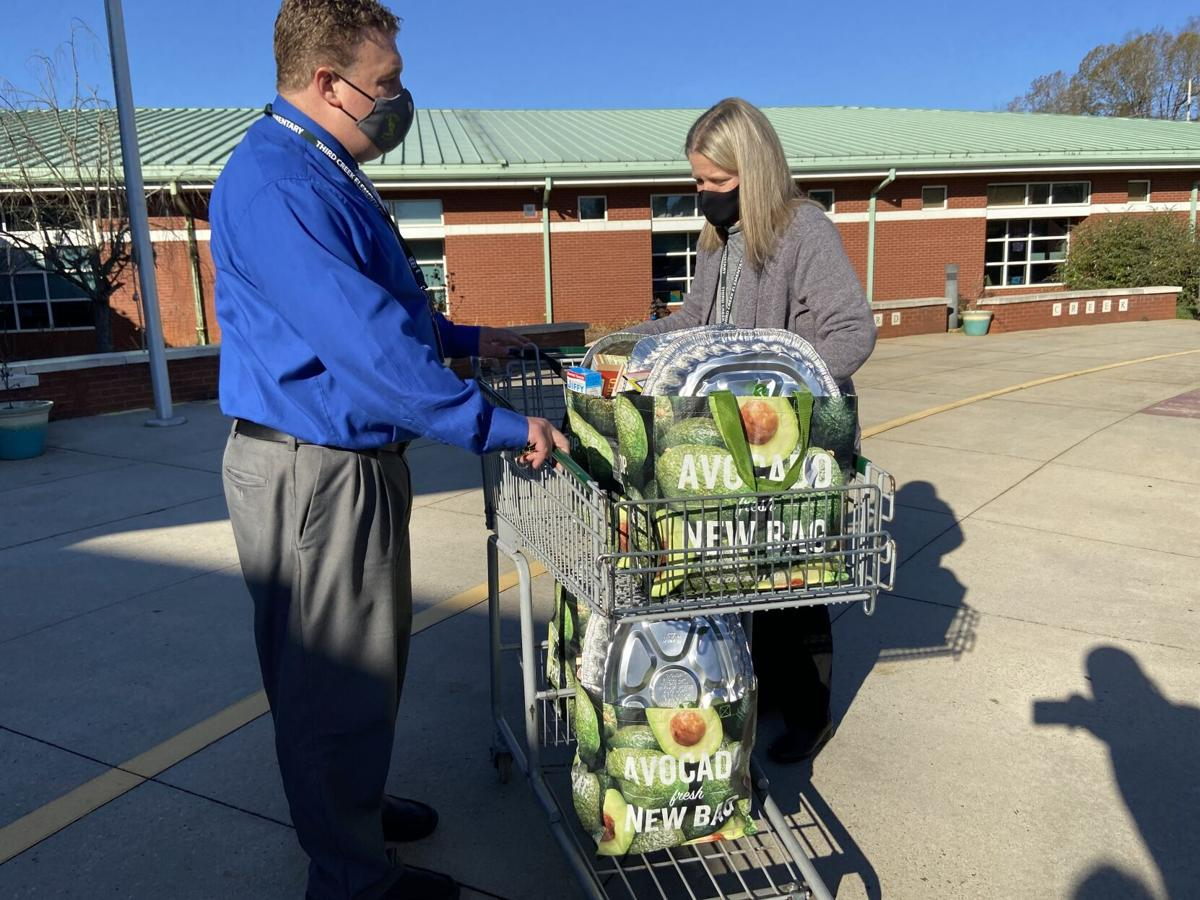 Lauren Jones delivers Thanksgiving meals to Third Creek Elementary School Principal Jason Humphrey in Statesville on Thursday.