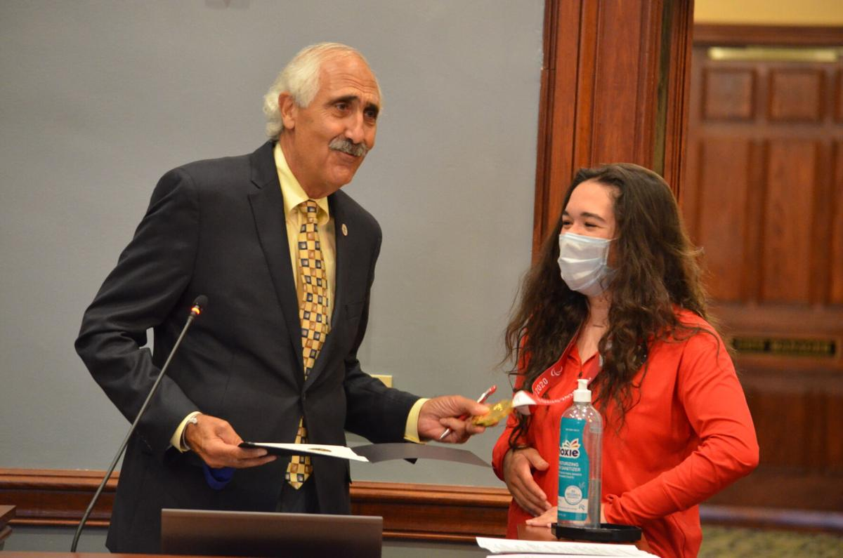 Mayor Costi Kutteh laughs with Emma Schieck during Monday's city council meeting in Statesville. Schieck won gold with the Women's Sitting National Team at the Tokyo Summer Paralympics this summer.