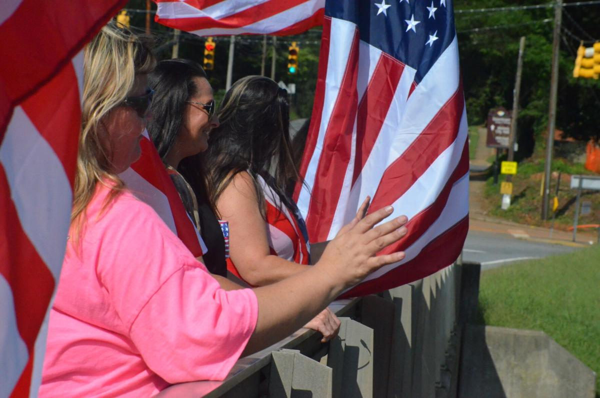 A group of women wave American flags