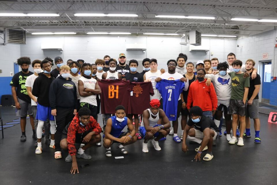 Brock Hoffman poses with members of the Statesville High School football team on Friday in Statesville.