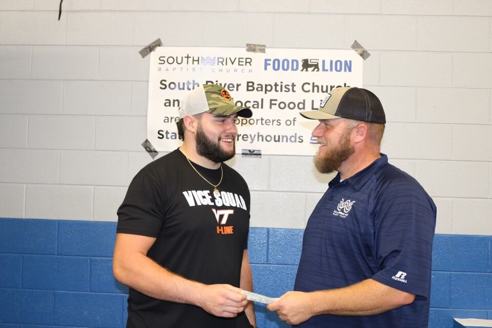 Brock Hoffman hands a check to Pastor Scott Townsell from South River Baptist Church.