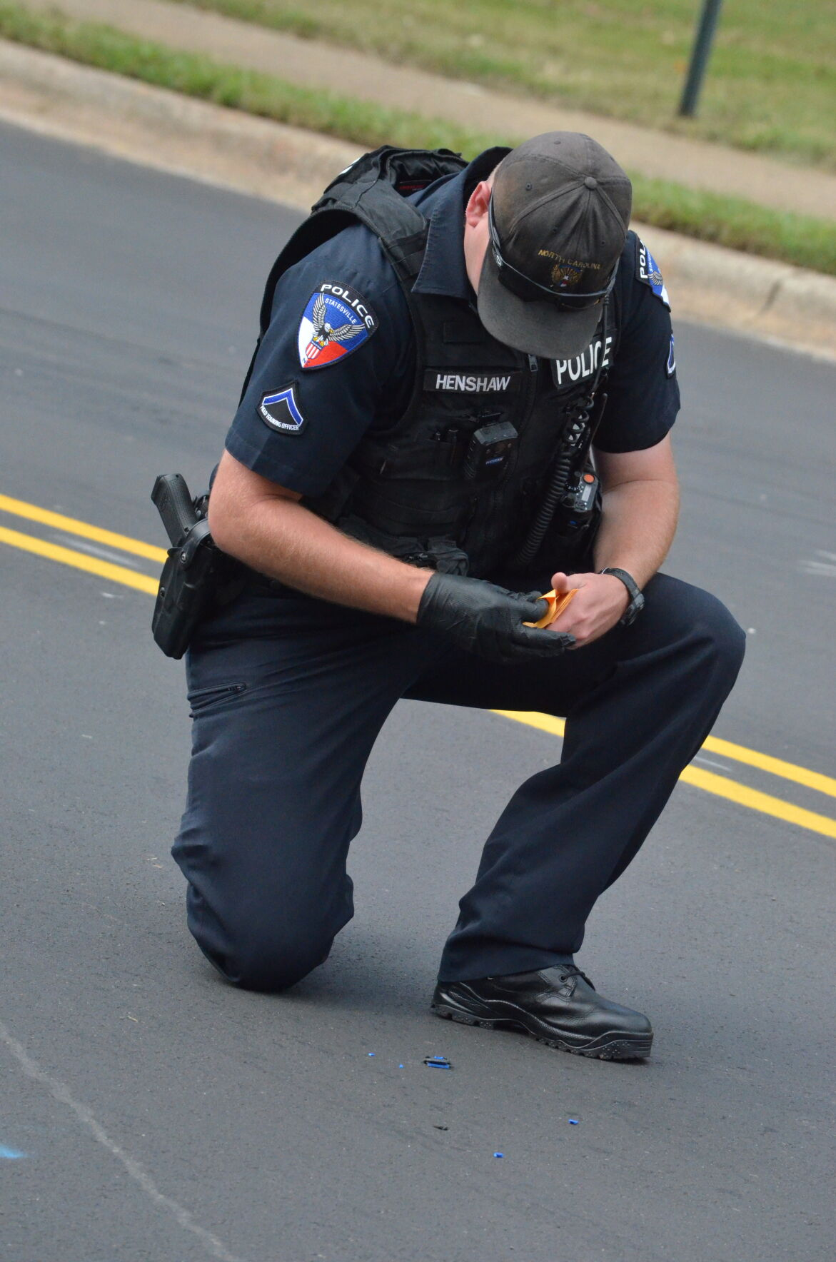 A member of the Statesville Police Department collects evidence on West Water Street in Statesville on Wednesday.