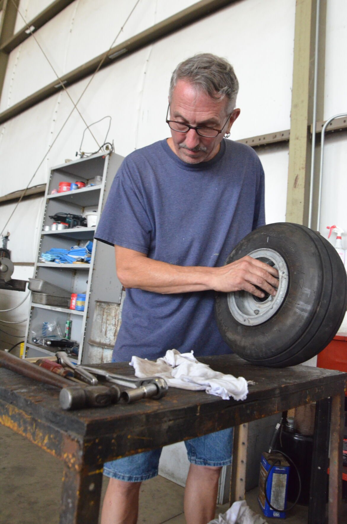 John Coulter works on an aircraft's wheel inside of a hangar at Statesville Regional Airport on Friday.