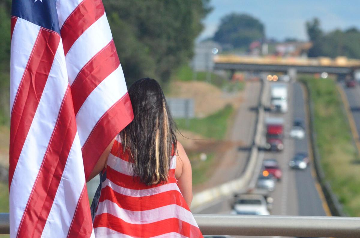 Jennifer Ward holds a flag on the Broad Street bridge over Interstate 77 in Statesville on Friday.