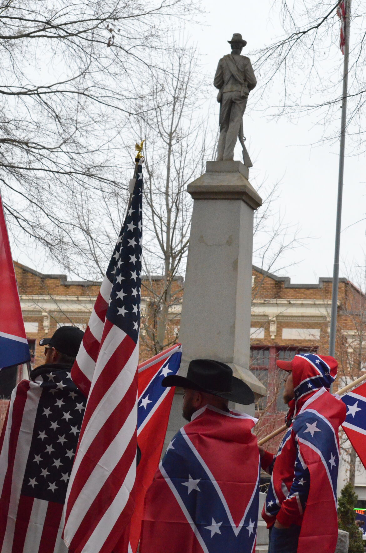 Men draped in the Confederate Flag stand behind the Iredell County Confederate Memorial at the Iredell County Government Center in Statesville on Tuesday.