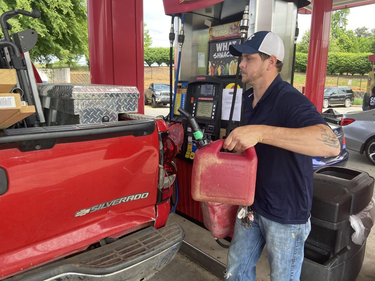 Devin Williams loads containers of fuel into his truck on Tuesday in Statesville.