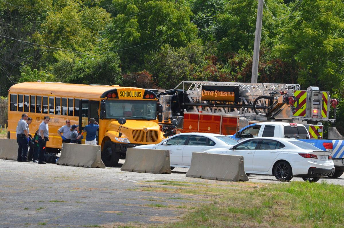 The Iredell-Statesville Schools bus sits along North Barkley Road in Statesville as first responders evaluate students for injuries.