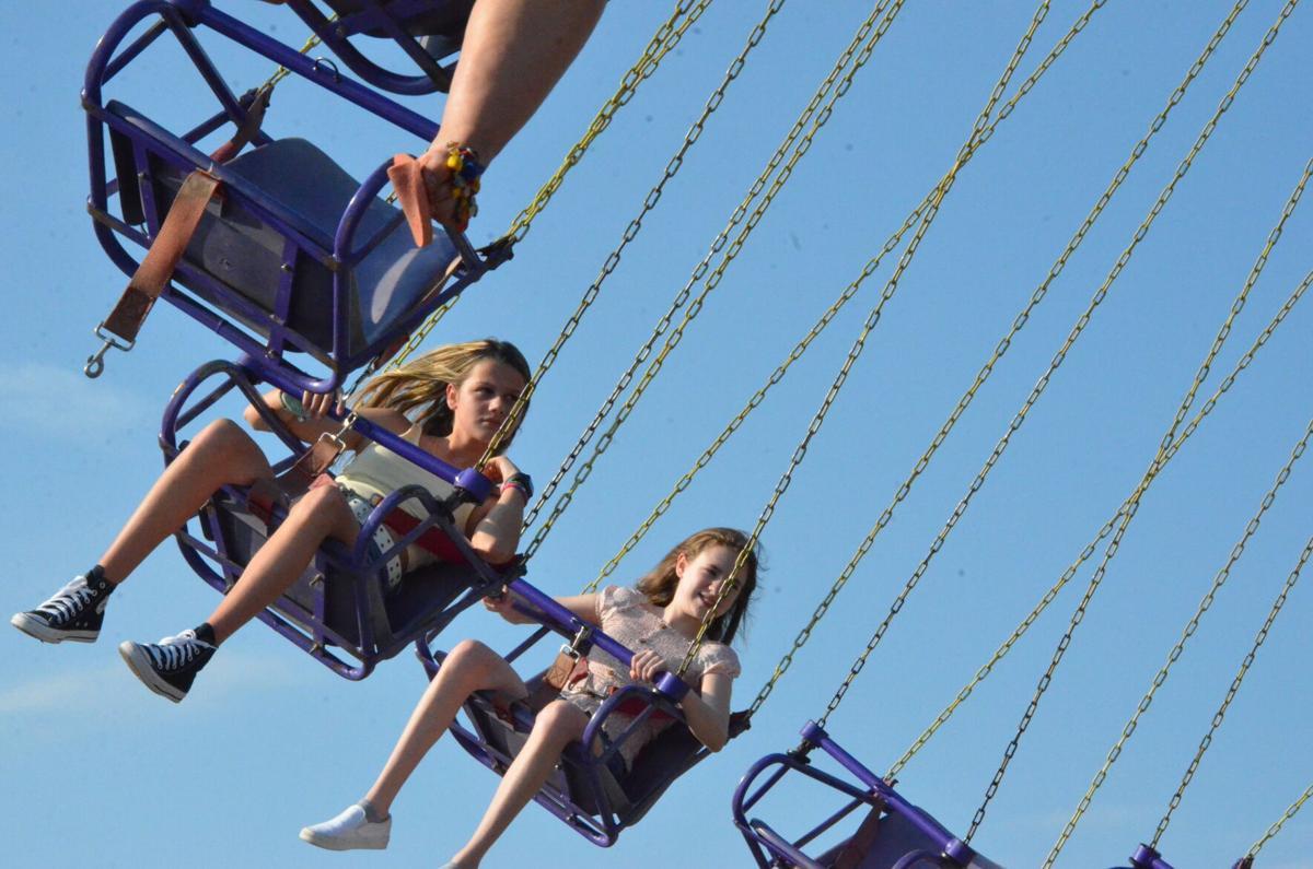 Aubrey Gibson and Nevaeha Kasmarcik ride the Yo-Yo at the carnival in Statesville on Saturday.