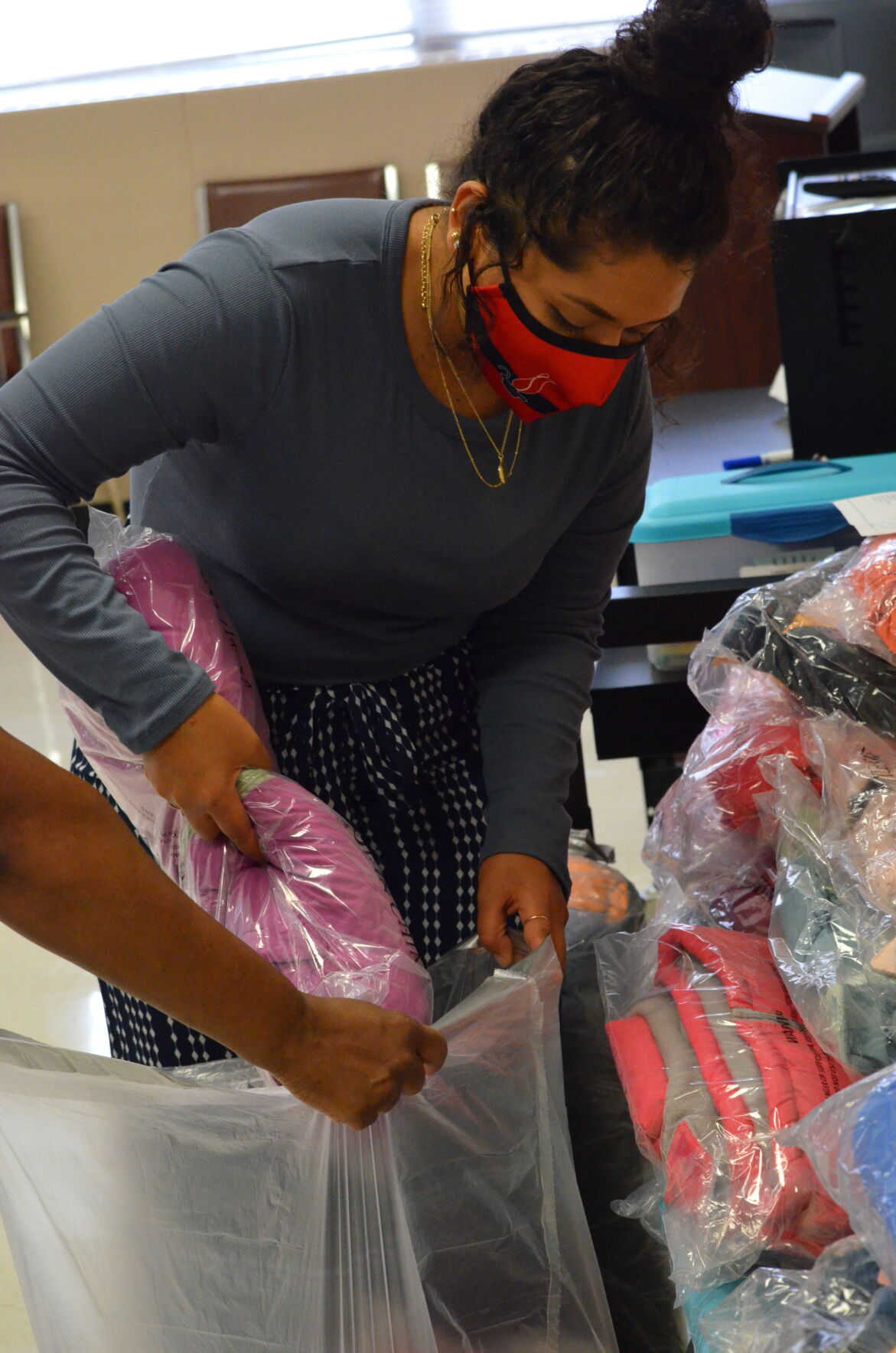 Paola Candelaria helps pack coats to be delievered to students in need at Iredell-Statesville Schools at the Allen D. Rutherford Education Center on Thursday.