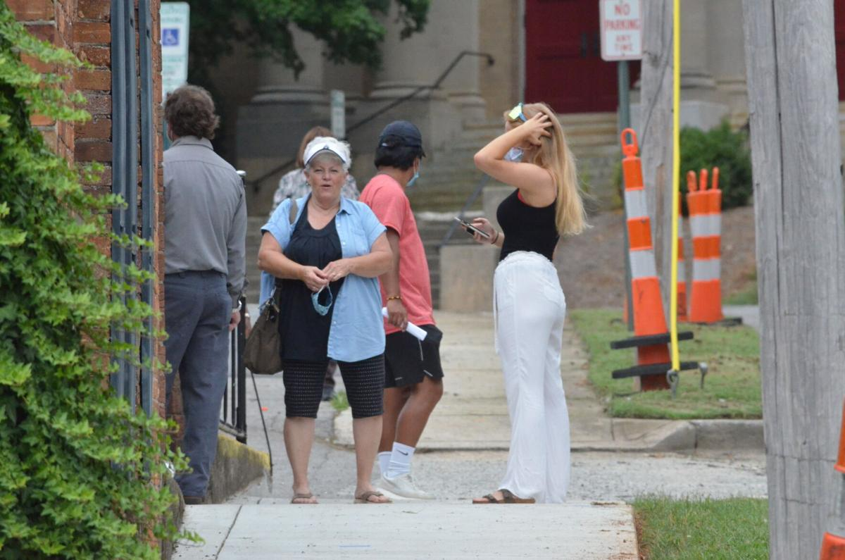 Customers wait outside the DMV Vehicle & License Plate Renewal Office on Friday in Statesville.