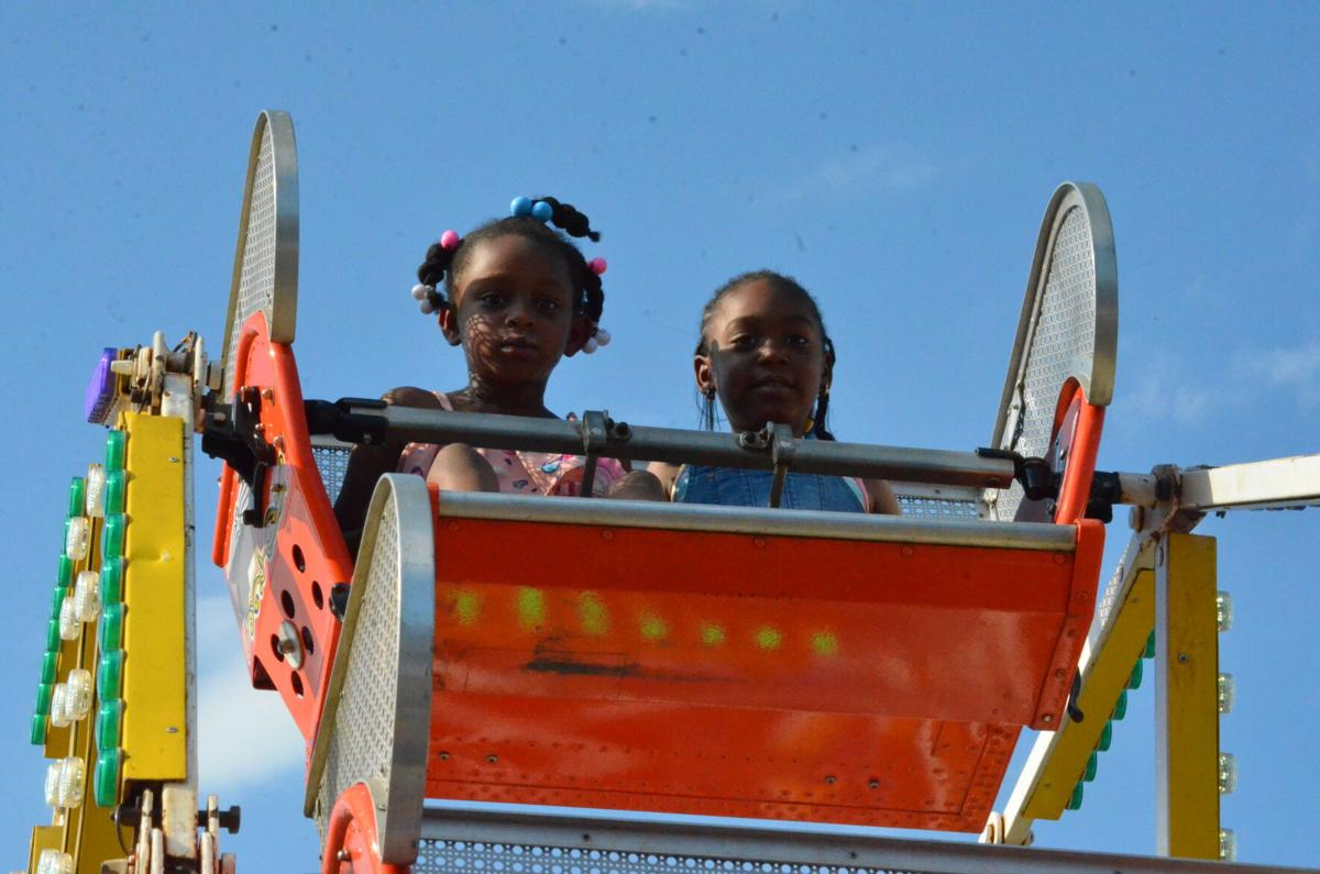 Bailee Jay Jamison, left, and Carsyn Turner ride a small Ferris wheel at the carnival in Statesville on Saturday.