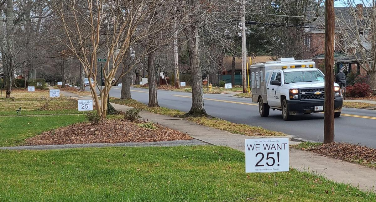 "Vehicles drive by some of the ""We want 25!"" signs John Gorman and others put in the yards on Davie Avenue."