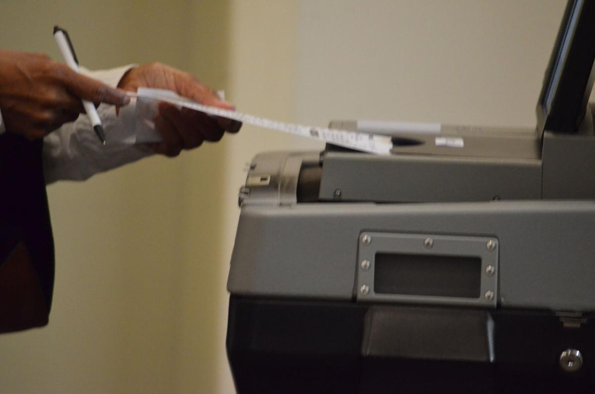 A voter prepares to submit their ballot on Thursday in Harmony.
