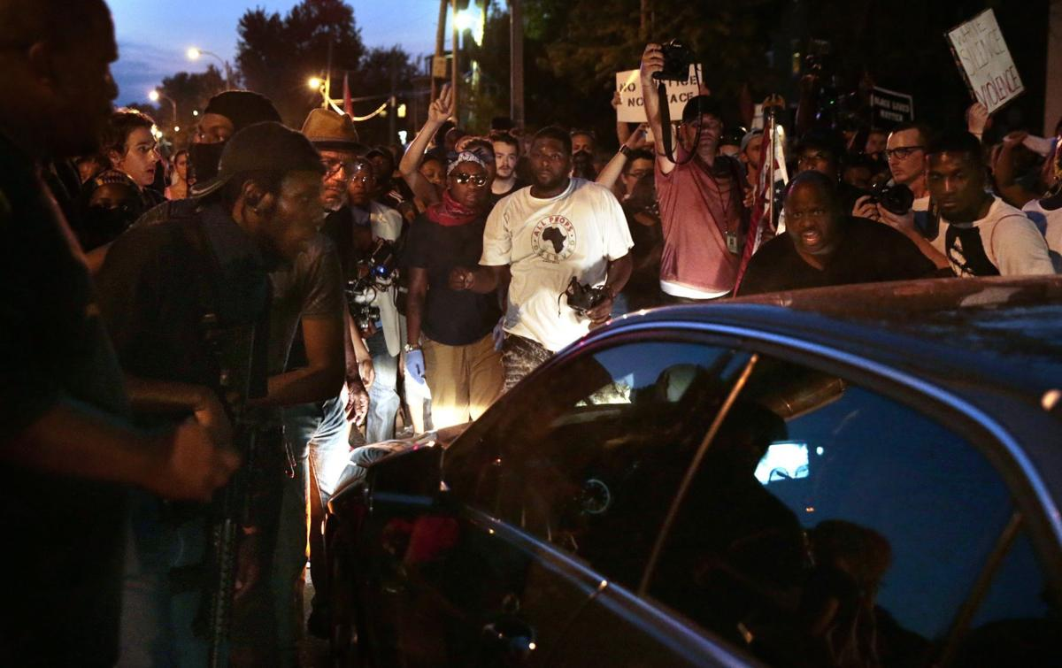 Protesters allow driver through march after seeing him armed