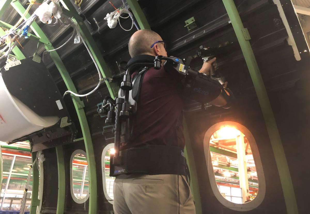 Employee Rob Gross gets a boost from a gas-powered exoskeleton Boeing is using to boost productivity and safety at their production factory in North Charleston