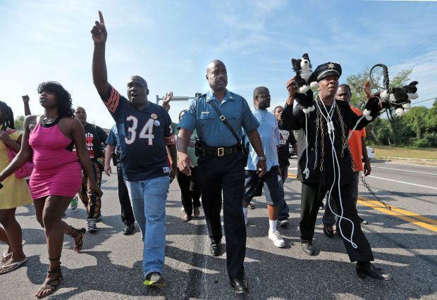 Missouri Highway Patrol Captain Ron Johnson marches with protesters