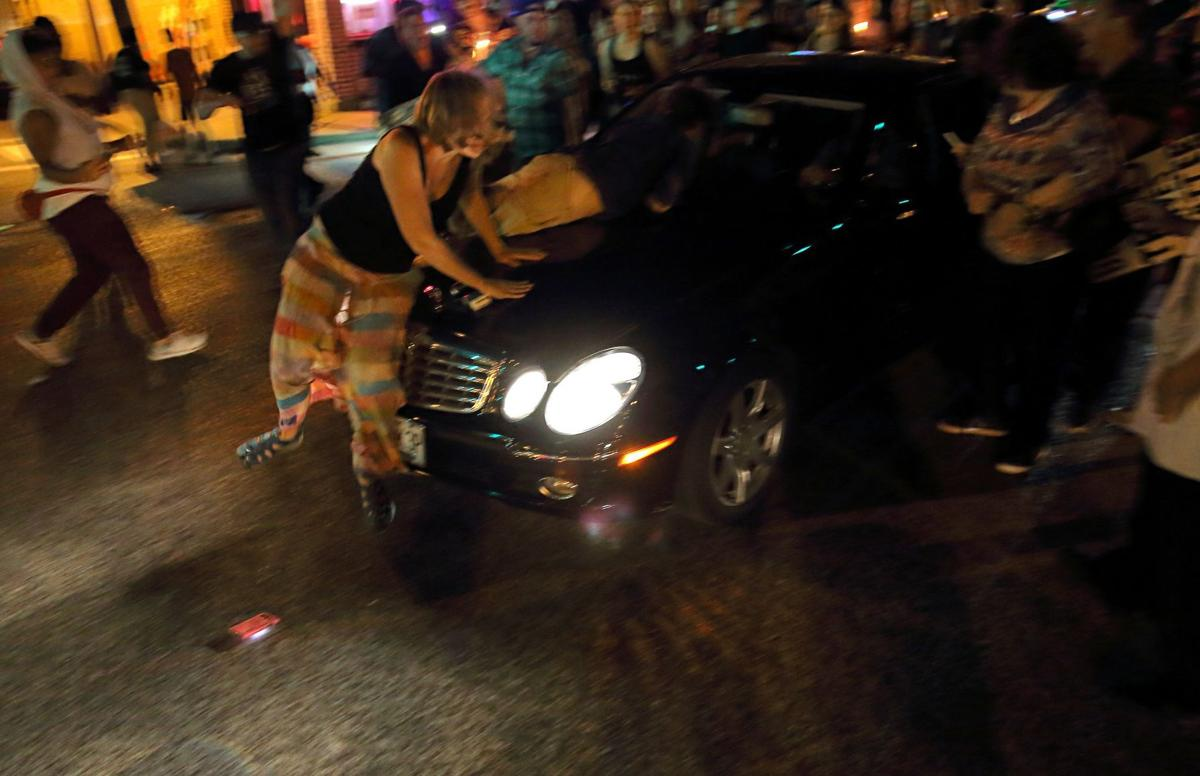 Car drives through protesters in st louis