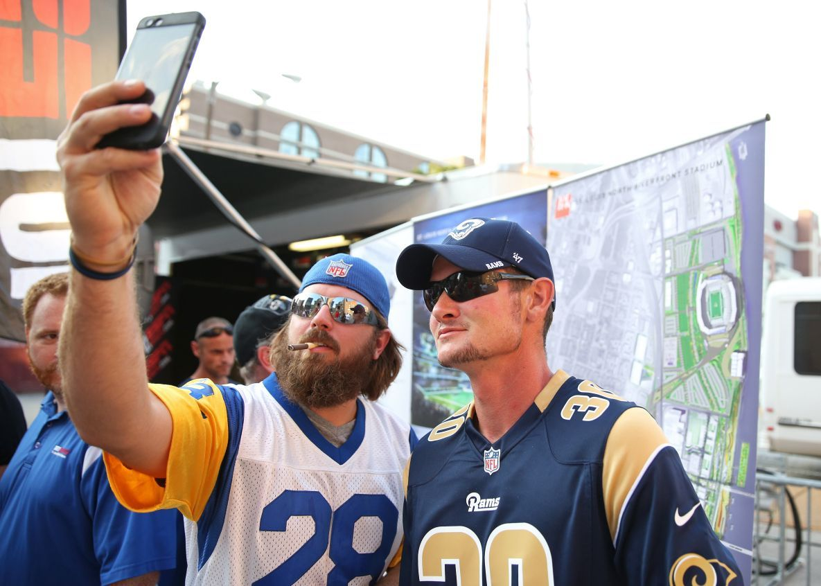 Rams fans take a photo of banner showing new stadium plans