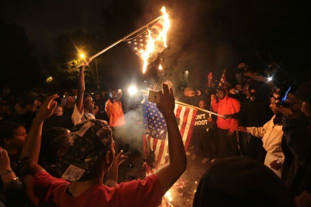 Marchers burn American Flags