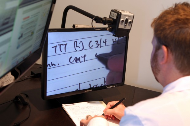 Dr. Terence Crowley uses a magnifier to read and write text