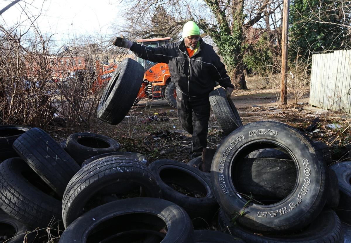 Christopher Smith removes illegally dumped tires
