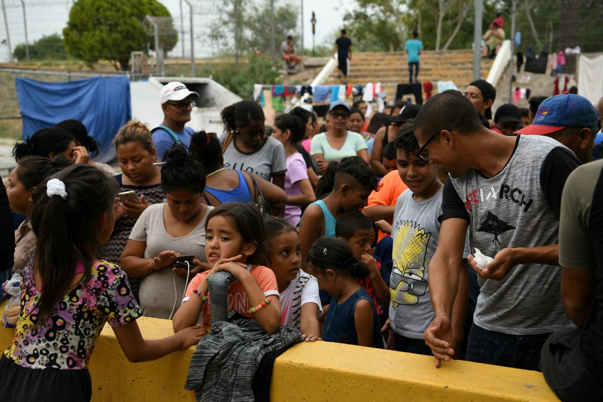 FILE PHOTO: Migrants, many of whom are asylum seekers sent back to Mexico from the U.S. under Migrant Protection Protocols (MPP), line up for a free meal provided by volunteers in Matamoros