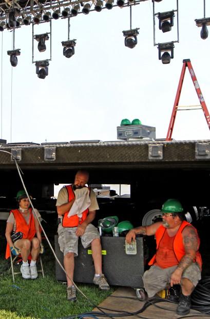 Prep work for 32nd annual Fair Saint Louis-audio engineers seek relief from heat under stage- vertical