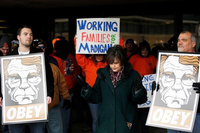 A woman, center, prays as she joins demonstrators protesting the possible re-election of Illinois of State Representative Michael Madigan as Speaker of the House at the University of Illinois campus