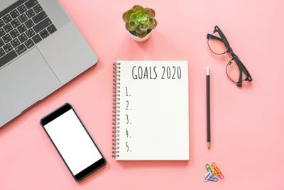 2020 New year concept. Goals list in stationery, laptop, notebook, smartphone, pot plant on pink pastel color with copy space
